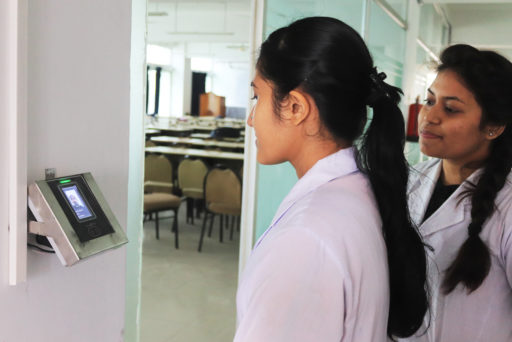 Student stands before the face regonition device for identity verification at class door