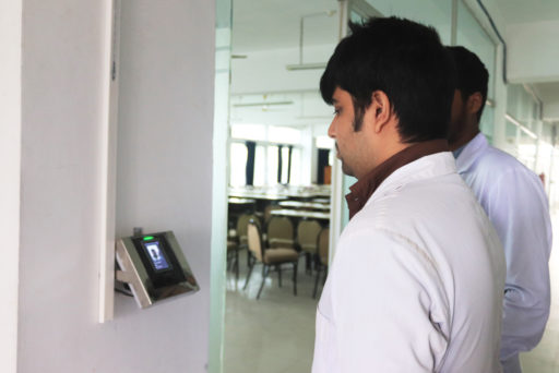The Student stands before the face regonition device for identity verification at class door