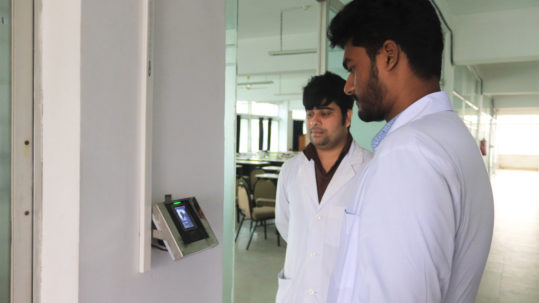 student stands in front of the face recognition camera for identity verification at class door
